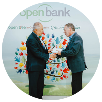 Two men shaking hands in front of an open tree